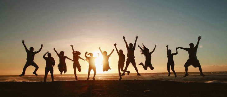 silhouette photography of group of people jumping during golden time