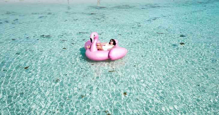 woman lying on pink flamingo bouy on body of water
